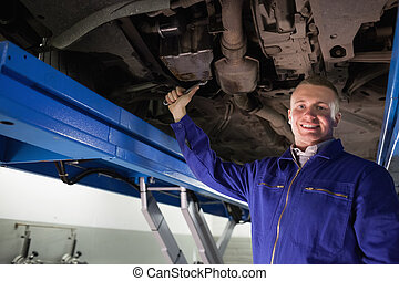Smiling mechanic repairing with a spanner