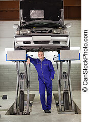 Smiling mechanic standing below a car in a garage