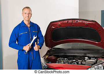 Smiling Mechanic Standing In Front Of Car