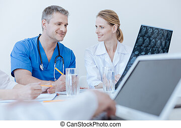 Smiling medical colleagues enjoying conversation at work