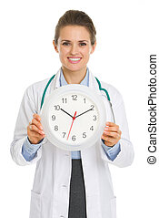 Smiling medical doctor woman showing clock