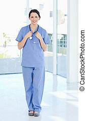 Smiling medical intern wearing a blue short-sleeve uniform