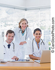 Smiling medical staff working on a laptop and a computer