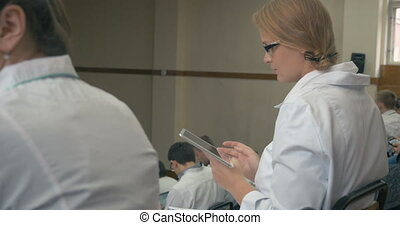 Smiling medical student with pad on the lecture