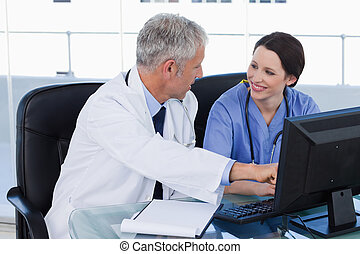 Smiling medical team working with a computer
