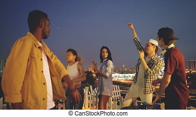Smiling men and women are dancing at night roof party celebrating holiday when deejay is working with digital mixing console. Nightlife, millennials and entertainment concept.