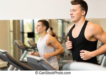 smiling men exercising on treadmill in gym - sport, fitness,...