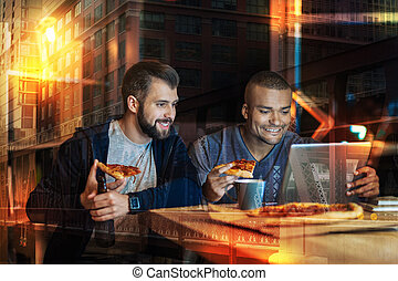 Smiling men looking at the screen while eating pizza together