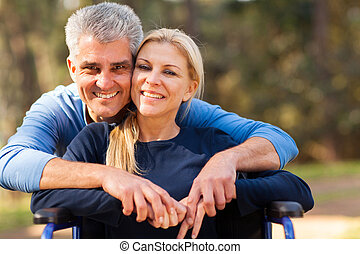mid age man and disabled wife - smiling mid age man and...