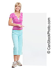Smiling middle age woman pointing on blank billboard