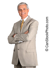 Portrait of a smiling middle aged businessman in a light suit with his arms folded. Three quarters view over a white background.