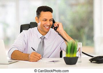 middle aged businessman talking on landline phone