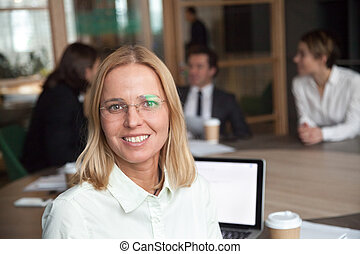Smiling middle-aged businesswoman executive looking at camera at