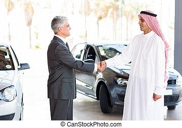middle aged car dealer handshake with arabian man