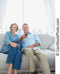 Smiling middle aged couple sitting on the couch watching tv at home in the living room