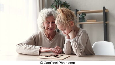 Smiling middle aged senior hoary grandmother playing wooden draughts on checkerboard with cute focused little preschool granddaughter, enjoying hobby boardgame pastime together in living room.