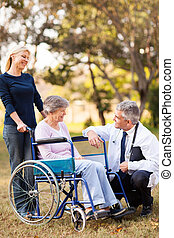 smiling middle aged healthcare worker talking to senior handicapped patient and daughter outdoors