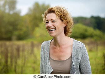 Smiling middle aged woman outdoors