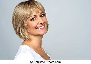 Pretty middle aged lady posing over grey background
