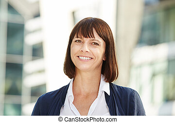 Smiling middle aged woman standing outside