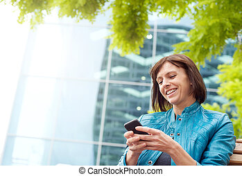 Smiling middle aged woman using mobile phone outside