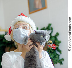 Smiling middle-aged woman wearing a medical mask and a Santa hat with a gray cat. Remote congratulations on Christmas. Pandemic.