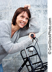 Smiling middle aged woman with bike