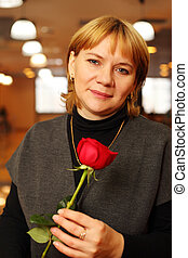 Smiling middleaged woman with red rose in hands stand in ...