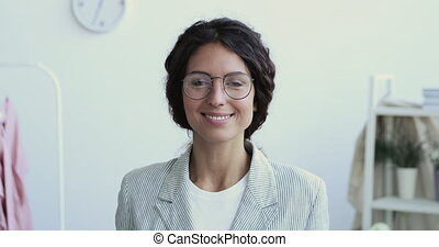 Smiling millennial creative occupation professional business woman looking at camera. Confident proud young happy female entrepreneur wearing glasses posing in office. Close up face front portrait.