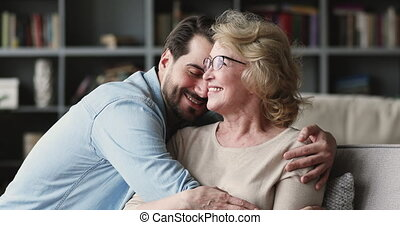 Happy young man visiting, coming to positive beautiful mature elderly mommy. Smiling millennial grownup son embracing, taking care of affectionate middle aged mother, relaxing on sofa at home.