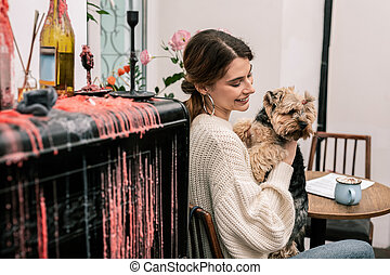 Smiling mistress holding her funny small dog
