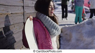 Smiling mixed race girl standing with snowboard in mountains...