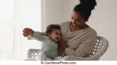 Smiling mixed race mother playing with adorable infant son...