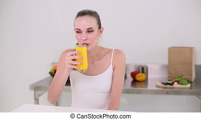 Smiling model drinking glass of ora