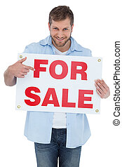 Smiling model holding a for sale sign
