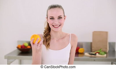 Smiling model smelling an orange at home in the kitchen