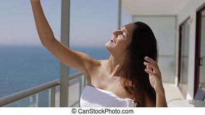 Smiling model taking selfie on balcony - Young brunette...