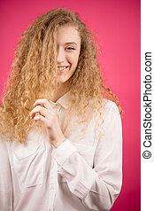 smiling model touching her curly blond hair