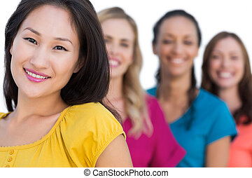 Smiling models in a line posing with focus on asian model