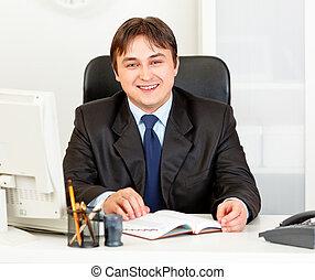 Smiling modern business man sitting at office desk