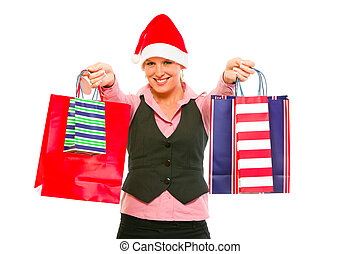 Smiling modern business woman in Santa Hat presenting shopping bags isolated on white