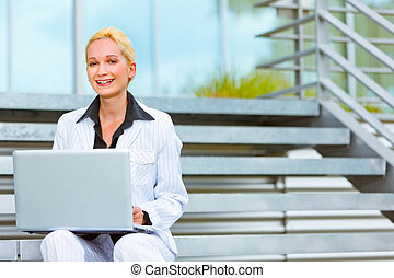 Smiling modern business woman sitting on stairs at office...