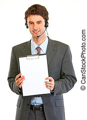 Smiling modern businessman in headset showing blank clipboard