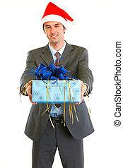 Smiling modern businessman in Santa Hat presenting gift