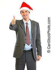 Smiling modern businessman in Santa Hat showing thumbs up