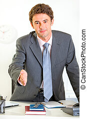Smiling modern businessman offer hand for handshake