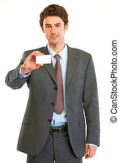Smiling modern businessman showing business card