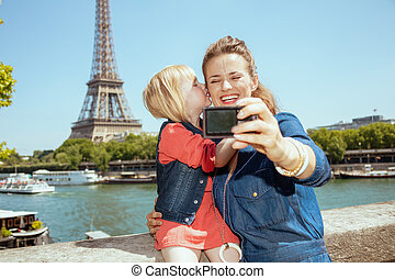 mother and child tourists taking selfie with digital camera