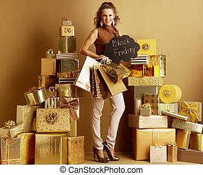 smiling modern shopper woman shopper showing Black Friday sign