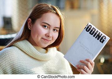 smiling modern teenage girl showing educational coding book